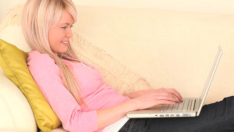 Blondhaired woman chatting on her laptop Stock Video Footage