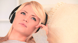 Attractive blondhaired woman listening to music Footage