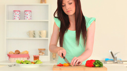 Young woman slicing vegetables Live Action