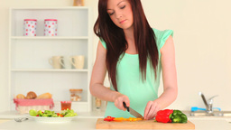 Young woman slicing vegetables Stock Video Footage