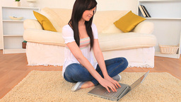 Attractive darkhaired woman chatting on her laptop Stock Video Footage