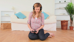 Blondhaired woman relaxing listening to music Footage