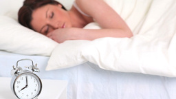Alarm clock ringing while a cute woman is sleeping Footage