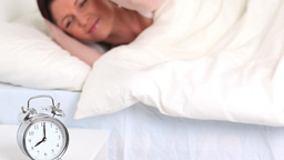 Alarm clock ringing while a cute woman is sleeping Stock Video Footage