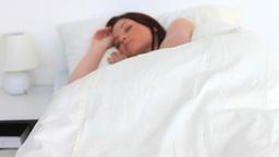 Attractive brunette sleeping in her bed Footage