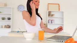Cute brunette talking on the phone while surfing o Stock Video Footage