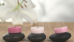 Candles raised on pebbles being lighted Stock Video Footage