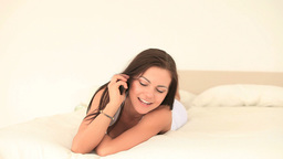 Attractive brunette woman on phone while lying on Stock Video Footage