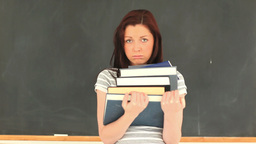 Depressed attractive woman holding some books Footage