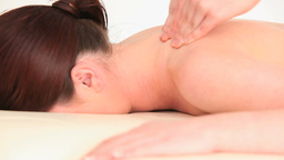 Young brunette woman receiving a massage while lyi Footage