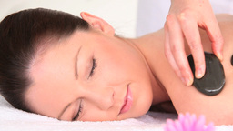 Good looking woman receiving a massage with pebbles while lying on a towel Footage