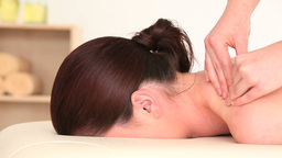 Young darkhaired woman receiving a massage while l Footage