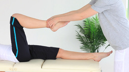 Young woman doing some exercises helped by a physi Footage