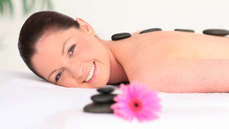 Good looking woman having some pebbles on her back Stock Video Footage