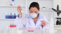 Good Looking Scientist Female Pouring A Liquid Fro stock footage