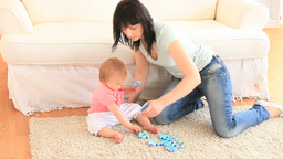 A mother and her daughter playing on a carpet Footage