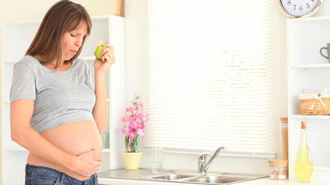 Pregnant woman eating an apple Footage