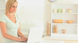 Blondhaired woman using her laptop Stock Video Footage