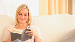 Smiling gorgeous woman reading a book Footage