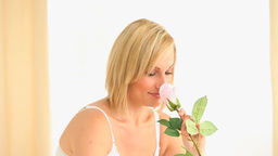 Blondhaired woman smelling a rose Footage