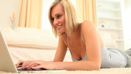 Cute fairhaired woman using her laptop Stock Video Footage