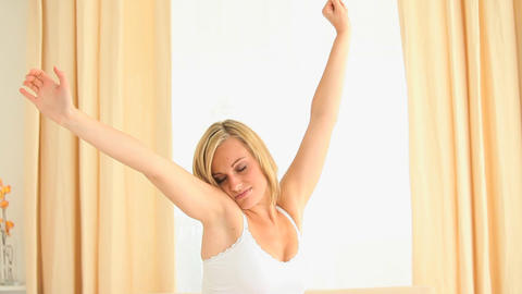 Young woman stretching her arms while waking up Footage