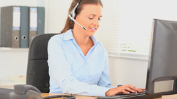 Office worker with a headset typing on her compute Stock Video Footage