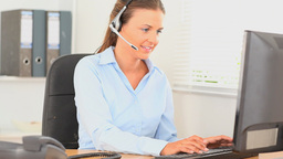 Office worker with a headset typing on her computer Stock Video Footage
