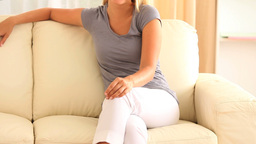 Cheerful blonde woman sitting on a sofa Stock Video Footage