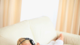 Woman lying on a sofa enjoying hearing music Stock Video Footage