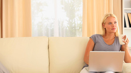 thoughtful woman sitting on a sofa with a notebook Stock Video Footage