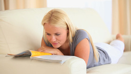 Blonde Woman reading a magazine lying on a sofa Footage