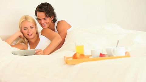 Happy couple together in bed with breakfast and ta Stock Video Footage