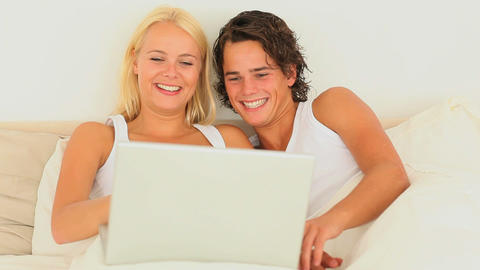 Cute couple sitting in bed with a laptop Footage