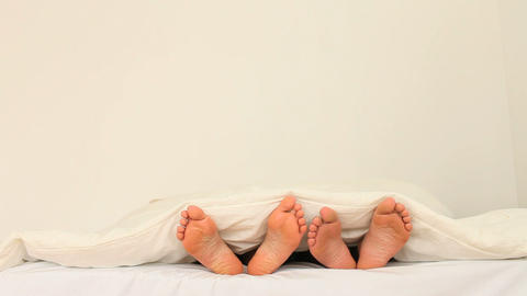 Two pairs of feet under a blanket Stock Video Footage
