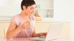 Woman drinking coffee while using a laptop Footage