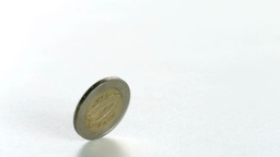 Two euro coin spinning on a white surface in slow  Footage