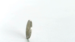 Two euro coin spinning on a white surface in slow Stock Video Footage