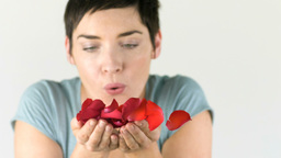 Woman blowing flower petals out of her hands Stock Video Footage
