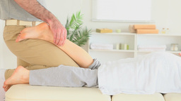 Chiropractor massaging a womans leg Footage