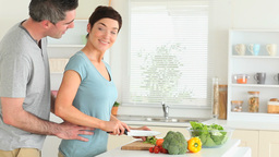 Woman preparing dinner when husband arrives Stock Video Footage