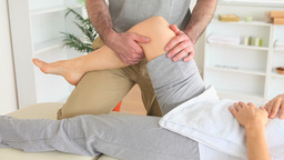 Chiropractor stretching the knee of a woman Stock Video Footage