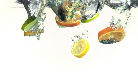 Slices of oranges, limes and lemons falling into w Footage