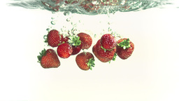 Strawberries falling into water in super slow motion Live Action