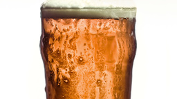 Overflowing glass of beer in super slow motion Footage