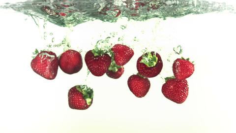 Red strawberries falling into water in super slow Stock Video Footage