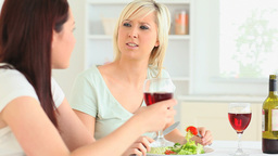 Young women eating salad and drinking wine Stock Video Footage
