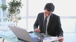 A business man uses a calculator to check his spre Footage