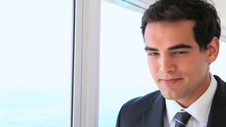 Man in a suit looks out the window then drinks Stock Video Footage