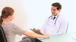 Doctor talks to a patient as he writes information Stock Video Footage